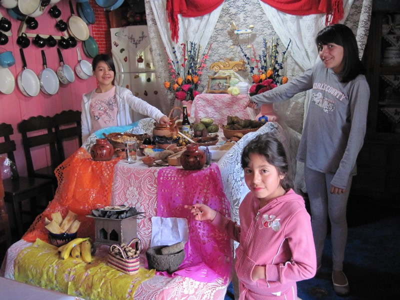 Families set up an ofrenda (shrine) to honor the memory of our deceased ancestors. Lupita invited Laura Emilia and Zamara to see her family's ofrenda.