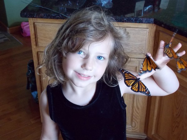Image of girl holding a monarch butterfly.